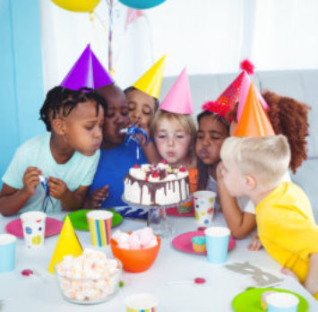 kids blowing a cake
